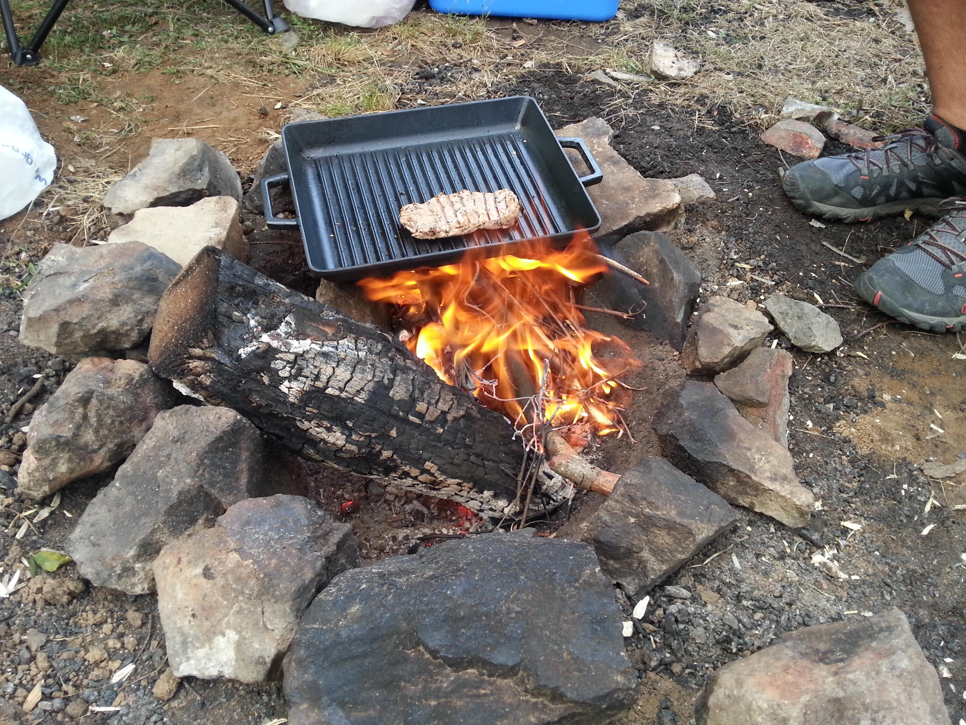 Ateş çukurunda yakılmış kamp ateşi ve üzerinde döküm tava